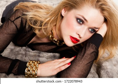 Glamorous young woman lying on bed, close up