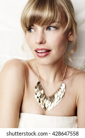 Glamorous young woman wearing gold necklace
