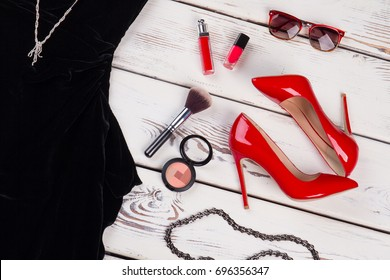 Glamour accessories for fasion party. Red heels, cosmetics, sunglasses, black dress, wooden background.
