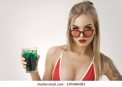 Glamour beach woman with perfect makeup wearing sexy red bikini and retro sunglasses holding cocktail, isolated on bright copy space background in studio. Gorgeous woman standing and posing looking at