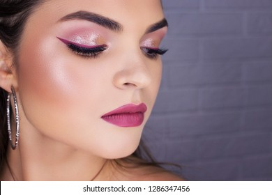 Glamour close-up portrait of beautiful woman model face with winged bright blue eyeliner make-up, clean skin on white background
