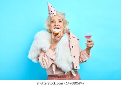 glamour crazy funny grandmother in stylish clothes celebrating her anniversary alone. close up portrait. isolated blue background. studio shot