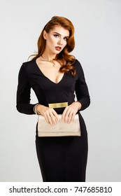 Glamour fashion portrait of elegant beautiful woman in evening black dress with golden little bag clutch. Perfect hairstyle and make up. Elegant style.