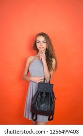 glamour and fashionable woman with black bag over red background