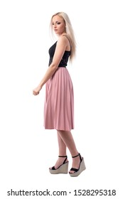 Glamour feminine blonde young woman in pink pleated skirt walking and looking down. Full body isolated on white background.