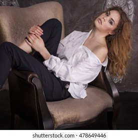Glamour girl in white blouse and black breeches barefoot in the studio