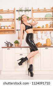 glamour hot woman posing in black fetish latex clothes as evil sexy mistress in the kitchen