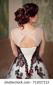 Glamour lady portrait in luxury open back dress. Beautiful model girl with perfect fashion makeup and hairstyle. Female Elegant wedding hairstyle for the wedding, unrecognizable rear view.