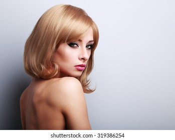 Glamour makeup female model with blond short hairstyle looking sexy with nude back on blue background