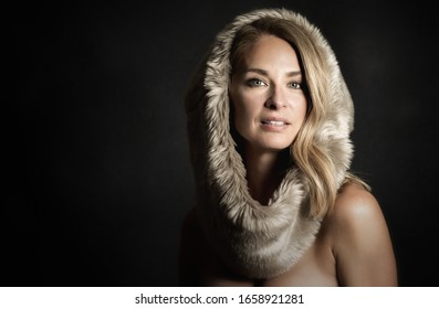 Glamour photo of a beautiful (middle aged) 45 years old blonde woman. With black background and room for text. She has bare shoulders and wear a hat in fur.