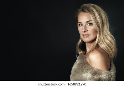 Glamour photo of a beautiful (middle aged) 45 years old blonde woman. With black background and room for text. She has bare shoulders and dressed in fur.