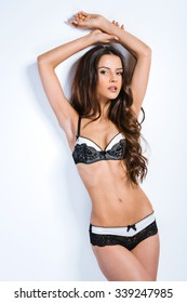 Glamour picture of beautiful slim young woman with long curly hair on white background. Girl wearing sexy lace underwear. Brunette looking at camera