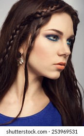 Glamour portrait of beautiful brunette woman with nice blue spring make-up and wavy hairstyle, braids. Fashion shiny highlighter on skin, sexy orange lip gloss and dark eyebrows