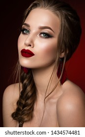 Glamour portrait of beautiful girl model with makeup and romantic hairstyle. Fashion shiny highlighter on skin, gloss lips make-up and dark eyebrows. Red lips