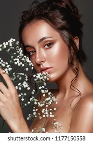 Glamour portrait of beautiful woman model fresh daily makeup, romantic hairstyle.  Fashion highlighter  skin, sexy gloss lips make-up. Cute freckles on young face. Sensual woman with white flowers