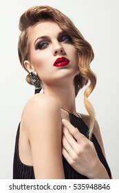 Glamour portrait of beautiful woman model with nice makeup and romantic wavy hairstyle. Fashion shiny highlighter on skin, sexy red glossy lips make-up and dark eyebrows, jewelry. Party look