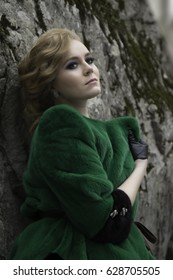 Glamour portrait of beautiful woman model with blond hair in luxury fur coat