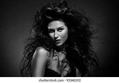 Glamour portrait of sexy beautiful young woman with long black hair model posing on dark background