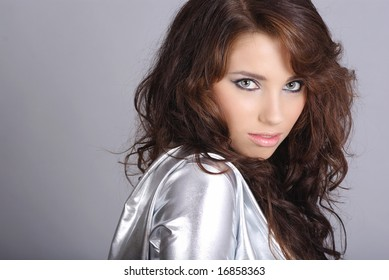 Glamour Portrait of sexy woman wearing silver clothing on grey background