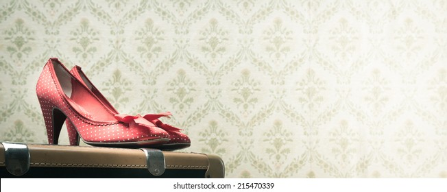 Glamour red dotted shoes on a vintage suitcase, retro wallpaper on background.