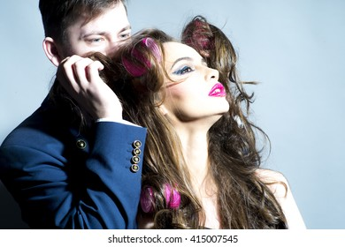 Glamour retro couple of attractive woman with fashionable makeup and hair curlers and man in suit
