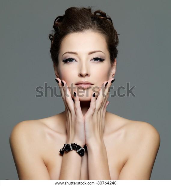 黒い爪とアイメイクを持つグラマーな色っぽい若い女性。前面のポートレート