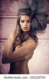 glamour shoot of very pretty woman with naked breast  and bizarre, big tulle accessory in the head. Fashion creative style
