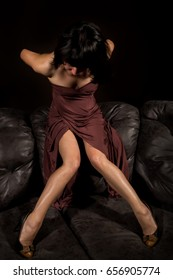 glamour woman in a brown dress leather sofa on a dark background