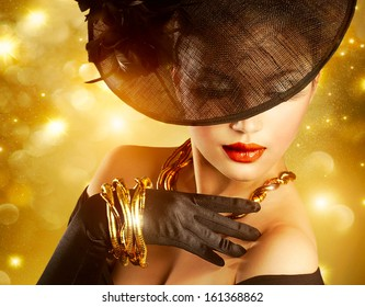 Glamour Woman Portrait over Holiday Gold Background.Luxury Golden Jewelry. Gorgeous Vogue Style Lady wearing Hat and Gloves. Jewellery. Vintage Styled Retro Girl