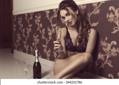 8b4bf7506868 glamour woman with sexy lingerie sitting on floor with a glass of champagne  in hand.