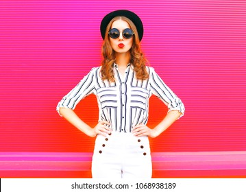 Glamour woman wearing a black hat sunglasses white pants over colorful pink  background