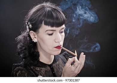 Glamour women lights a cigarette on black background