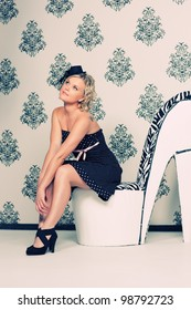 Glamoured retro styled portrait with blond model sits on high heel shoe