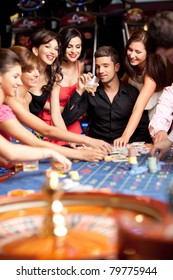 glamourous laughing friends plying betting at roulette table