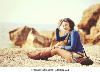 glamourous portrait of the young beautiful woman in leather boots on the bank of a beach