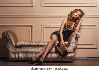 Glamourous portrait of the young beautiful woman in leather shoes and stylish handbag. Trend fashion look. Black dress.