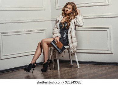 Glamourous portrait of the young beautiful woman in leather boots and stylish handbag. Trend fashion look. Beauty Fashion Model Girl in White Mink Fur Coat. Beautiful Luxury Winter Woman