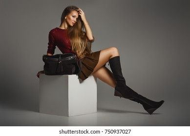 Glamourous portrait of the young beautiful woman in leather boots and stylish handbag. Trend fashion look.