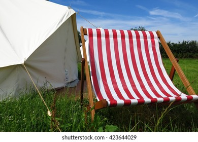 Glamping camping at Glastonbury Festival canvas tent deck chair summer field sunny day
