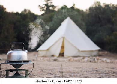 Glamping lifestyle. Boiling kettle with steam near big retro camping tent. Luxury travel accomodation into the forest.