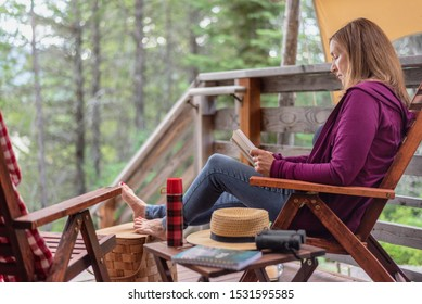 glamping trip - woman relaxing outside cabin in the woods with a book on vacation