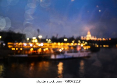 Glare at night city. Reflection of the night city in the river. Bokeh. Abstract background. A glowing garland.