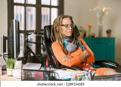 Glaring professional with dreadlocks in her office