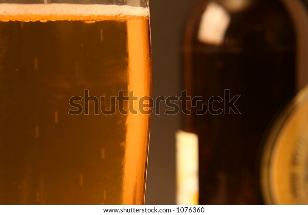 Glas of beer and a bottle (focus on the glas)