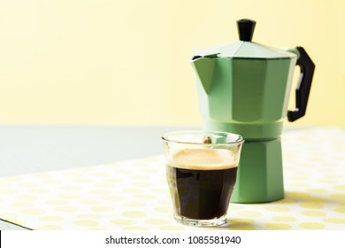 Glas of coffee and percolator on sunny yellow blue background