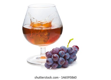 Glas of cogniac wih a splah caused dropped ice and bunch grape. On the white background