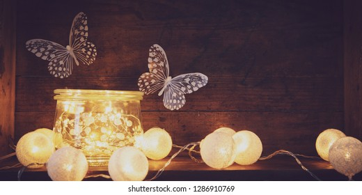 glas filled with lights and butterflies in background on wooden board  love thems