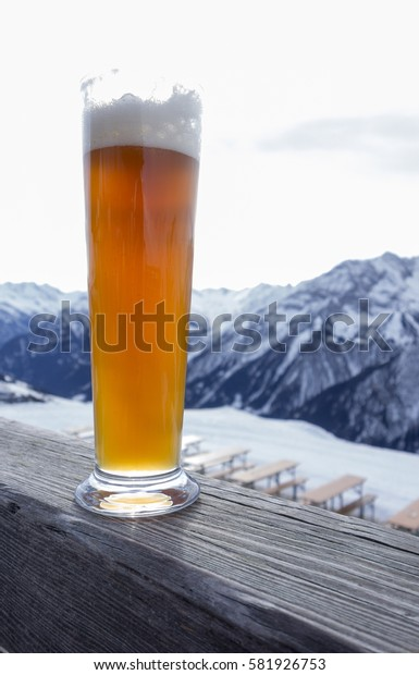Glas of hell natuurtrub weiss beer in the alps on wooden fence