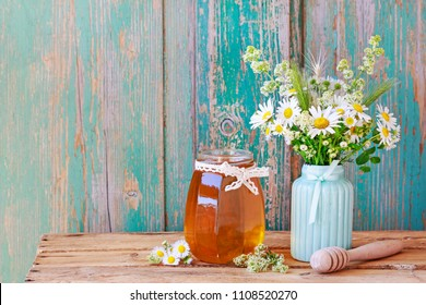 Glas jar with honey and bouquet with chamomiles and other wildflowers.
