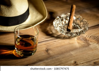 glas of rum, cigar and a panama hat in a bar in Cuba